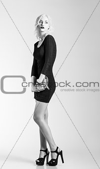 Studio fashion shot: beautiful girl in black dress with clutch in hands. Black and white