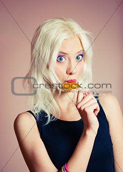 Closeup portrait of cute blonde girl with candy