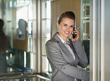 Smiling business woman talking cell phone in elevator