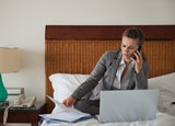 Business woman working with documents on bed in hotel room