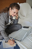 Smiling business woman having working phone calls on bed in hote