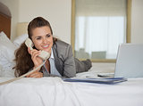 Business woman laying in bed with laptop and talking phone in ho