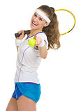 Happy tennis player with racket and ball pointing in camera