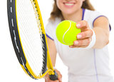 Closeup on racket and ball in hand of tennis player ready to ser