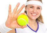 Closeup on ball in hand of smiling tennis player