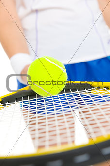 Closeup on tennis player balancing ball on racket