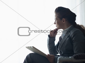 Silhouette of thoughtful business woman with tablet pc