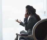 Silhouette of business woman talking cell phone. rear view