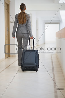 Business woman walking with bag on wheels. rear view