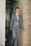 Smiling business woman with bag on wheels exit elevator