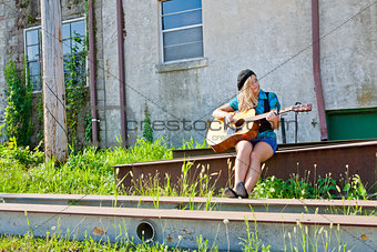 Blonde Girl Playing Acoustical Guitar