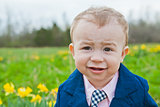Little Boy in Blue Suit Smiling in a Field of Daisy Flowers