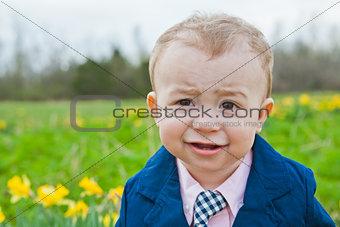 Little Boy in Blue Suit Smiling in a Field of Daisy Flowers