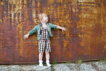 Little Girl in Green Jacket and White Socks by a Wall