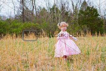 Little Girl in Pink Dress Dancing in a Field