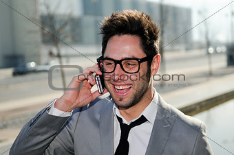 Portrait of handsome man in urban background talking on phone