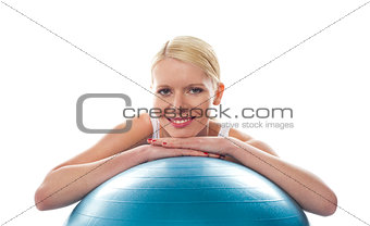 Attractive fit young woman resting chin over ball