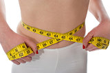 Closeup of tape measure around woman waist