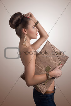 fashion brunette in jeans with big bag in profile