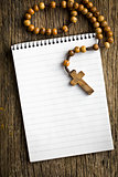 rosary beads and blank notebook