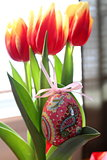 Easter egg decoration hanging from tulips