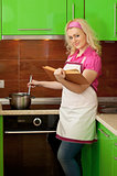 Blonde reading a book and preparing food on kitchen