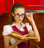Young girl with a book on kitchen