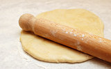 Wooden rolling pin dusted with flour, ready to roll out fresh pastry