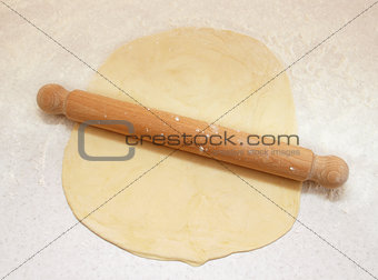 Block of freshly made pastry rolled out on a floured work surfac