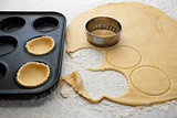Pastry circles being cut and filling a bun tin to make jam tarts