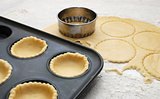 Pastry circles cut and lining a metal bun tin