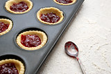 Filled, uncooked jam tarts in a tin