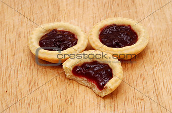Three jam tarts, one with a bite taken, on a wooden table