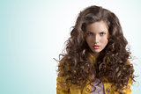 wavy brunette with yellow jacket looks in to the lens
