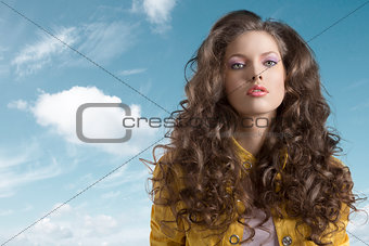 wavy brunette with yellow jacket in front of the camera