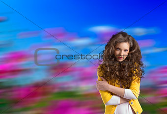 wavy brunette with yellow jacket and crossed arms