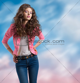 wavy brunette with yellow jacket and hands on the hip