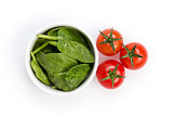 fresh spinach leaves in bowl and tomatoes
