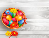 Easter background with color easter eggs in basket on wooden tab