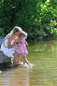 mother and her little daughter squirt water at the lake
