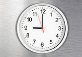 Classical clock on metal background displaying nine o'clock