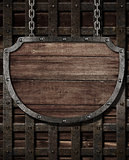 aged medieval shield signboard hanging on wooden gates