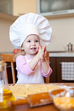 Little girl clears hands in kitchen 