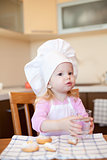 Little girl drinks water in kitchen