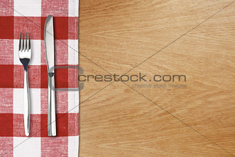 Fork and tableknife on red gingham tablecloth. Wooden table top