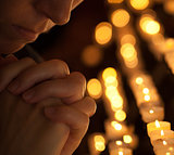 Woman praying in church cropped part of face and hands closeup p