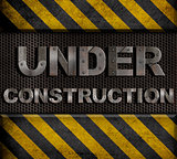&quot;under construction&quot; metal text with rivets over grid