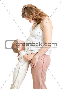 Little boy hugging pregnant mother's belly and looking up