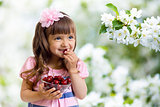 little girl with cherry berries bowl in apple garden