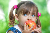 Little girl portrait eating red apple outdoor